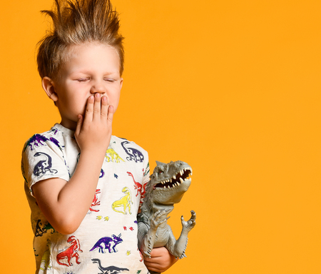 little boy with funny, disheveled hair, yawns only with woke up, holds a toy plastic dinosaur as a portrait. boyish Stock Photo
