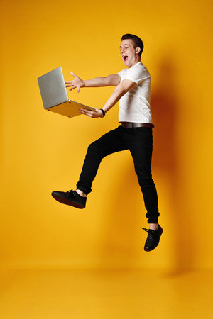 Full length of a smiling young student working, isolated on yellow background, working on a laptop, late for classes Stock Photo