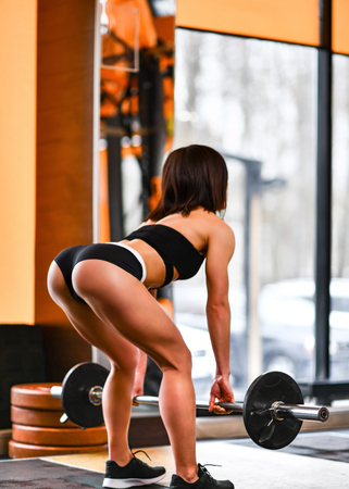 young pretty slim Athletic girl in black sportswear is training with a barbell in the gym Imagens