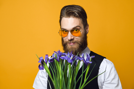 brutal bearded young man in yellow stylish glasses and a tank top holds a bouquet of irises flowers on a yellow studio background.