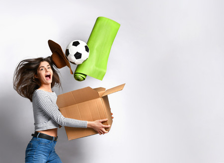 woman is infinitely happy to move to her new dream home. She jumps for joy holding a cardboard box with things - a hat. ball. plant. yoga mat. The concept of relocation. packing things