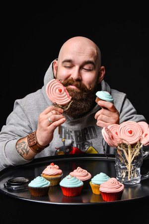 Moscow, Russia, April 2015 - A happy bearded bald man in a sweater hoodie with a picture of Angry Birds holding two cream cakes and trying one of them, enjoying the taste. on a black background.