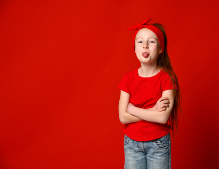 Cute funny red-haired girl in a red bandage on her hair and a red T-shirt jokingly shows your tongue. On a red background. Imagens