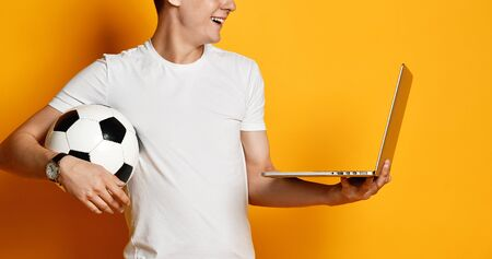 young man of the 20s in a white T-shirt, holding a laptop and a soccer ball, clung to the screen - closely watching watching the transfer on the screen. worried