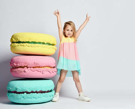 Cute little girl in bright clothes have fun at the birthday party fun room decoration candy macarons.