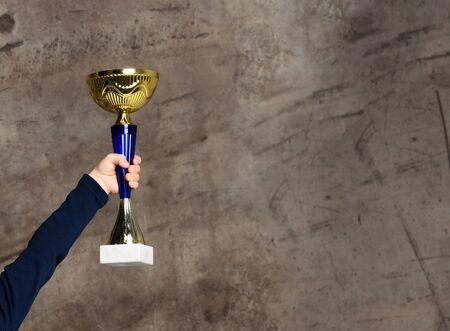 Close-up boy kid hand holding golden Trophy on concrete background Stock Photo