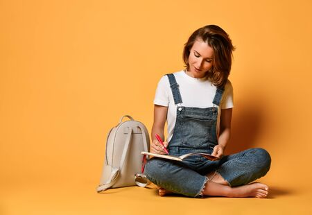 Portrait of a pensive girl in a white T-shirt and denim overalls, sitting on the floor with a kransny notebook and a pencil on a yellow background and writing something Zdjęcie Seryjne