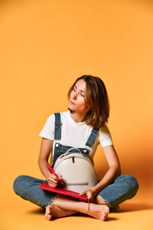 Portrait of a pensive girl in a white t-shirt and denim overalls, sitting on the floor with a crown pad and a pencil on a yellow background Standard-Bild - 129164771