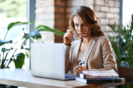 Confident young woman in smart casual clothes, working on a laptop, sitting by the window in a creative office or cafe, wearing a jacket, drinking coffee Stockfoto