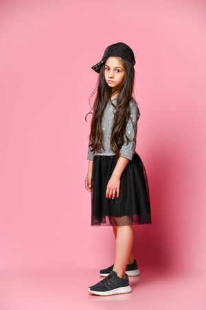 Portrait of a little hipster girl in a dark dress with a baseball cap and sneakers, on a pink background. studio