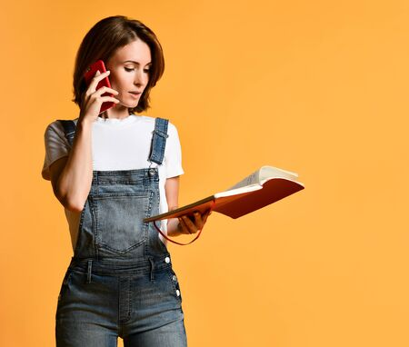 Young smiling woman talking on a mobile phone, sending text messages to friends, wearing a casual white T-shirt and denim overalls, has a red manicure, isolated against a yellow background