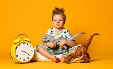 Little cute boy in pajamas holding a toy dinosaur in his hands, sitting on a pillow with an alarm clock. Early rise. Isolated on a yellow background.