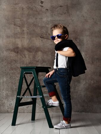 Cute stylish boy in a white T-shirt, jeans for suspenders and sneakers, holding a jacket over his shoulders, wearing sunglasses from the sun and sits on a chair near the concrete wall