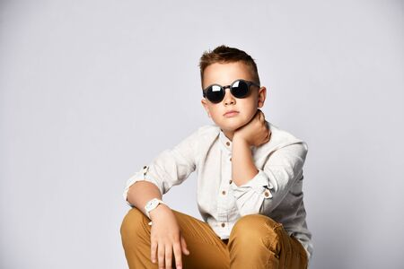 Cute stylish boy ten-year-old in a white linen shirt and mustard-colored trousers and sunglasses sits on a chair near the light wall Imagens