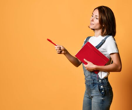 young beautiful woman standing, holding a red notebook textbook in her hand and points the pen to the side, side view