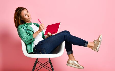 happy young woman is sitting in a chair dangling her legs thinking about something, writing everything in a notebook. Female student dressed in casual jeans and bomper jacket