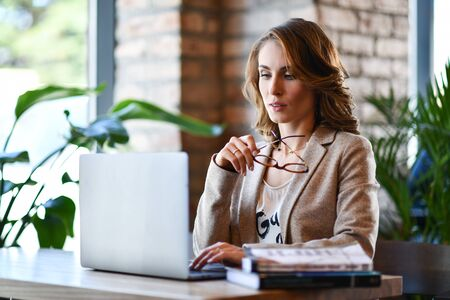 Confident young woman in smart casual clothes, working on a laptop, sitting by the window in a creative office or cafe, took off her glasses