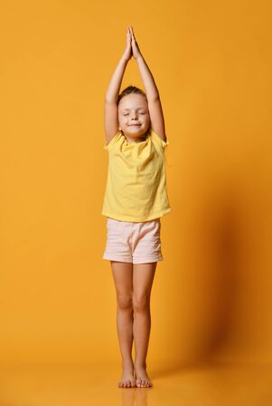 Smiling girl practicing yoga, standing in a pose of a mountain, arms up, eyes closed, working out wearing sportswear, t-shirts, pants, yellow studio background Stock Photo