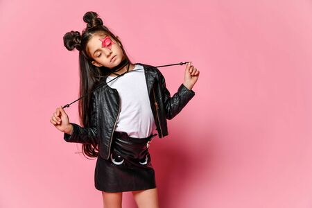 Little hipster girl in a black leather jacket posing on a pink background, holding the ties from the necklace