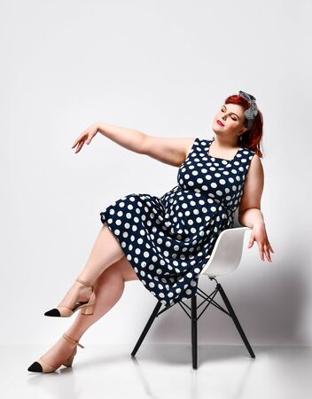 cute young plus-sized girl wearing a polka-dot dress and American-style hair band. She sits on a chair and shows to the side. Advertising. Reklamní fotografie