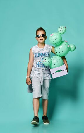 Cheerful boy boy teenager in summer lunch shorts and tank top holding green cacti-shaped balloons in a box