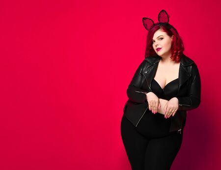 Cute sexy plus size brunette with black bunny ears in leather jacket and underwear posing on red background. 版權商用圖片