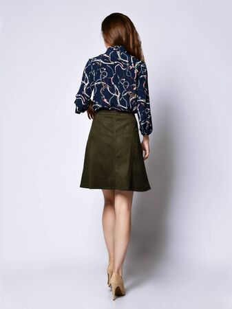 Woman back in in a dark silk blouse with floral patterns, a dark short green skirt with buttons and high-heeled shoes, looking with a smile