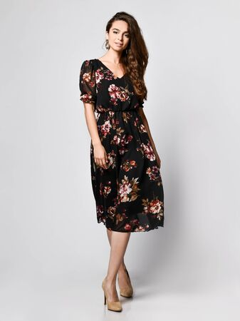 Slim curly female model in a silk dark long dress looking at the camera in full growth. . Cute girl in romantic clothes is going on a date, smiling pretty on a white background.