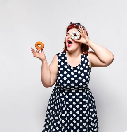Portrait of beautiful cheerful fat plus size woman pin-up wearing a polka-dot dress isolated over light background, eating a donut. unk food, Slimming, weight loss