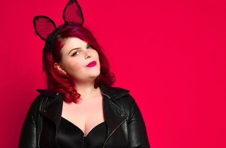Cute sexy plus size brunette with black bunny ears in leather jacket and underwear posing on red background. 写真素材