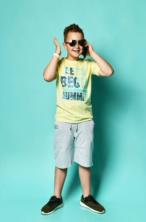 Portrait of a cool young teen guy talking on a mobile phone in summer style clothes in sunglasses, on a blue background