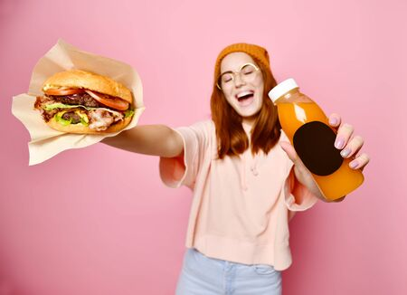 Beautiful teenage girl with red hair and hat holding burger and beverage in both hands. Ginger student girl has fast food lunch