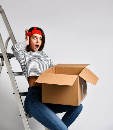 Surprised young brunette woman holding a cardboard box on a light background, sitting on an iron staircase ladder. We are preparing for repair and moving. Delivery and unpacking. Stock fotó