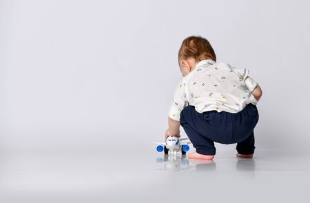 little toddler boy sits on a light wall background in an empty room with a toy airplane 版權商用圖片