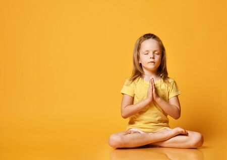 Little girls practicing yoga with closed eyes, sitting in the lotus position with legs crossed, preparing for training, working out wearing sportswear, t-shirts, pants, yellow studio background.