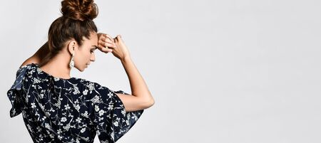 curly female model in a silk dark floral dress is looking at the camera from behind her shoulder. Lovely girl in romantic clothes smiling pretty on a white background. Stock fotó