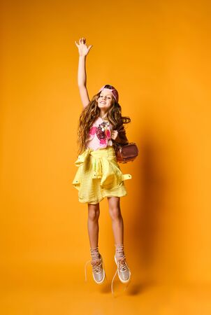 Charming fashionable teenager girl in skirt and sneakers joyfully jumping over yellow studio background 写真素材