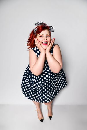 Cute portrait of a full-length red-haired woman plus size in a retro polka-dot dress, joyful smiling at the camera. Pin up girl vintage. Reklamní fotografie