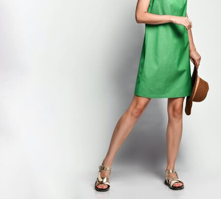 Cropped photo of a model in a green casual dress with a straw hat in her hands. Lovely girl in romantic clothes goes on a date, to the office, to a meeting. Urban fashion