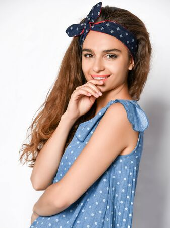 Cute young curly girl in a polka dot denim summer dress looking playfully at the camera. . Cute girl in romantic clothes is going on a date, smiling pretty on a white background.