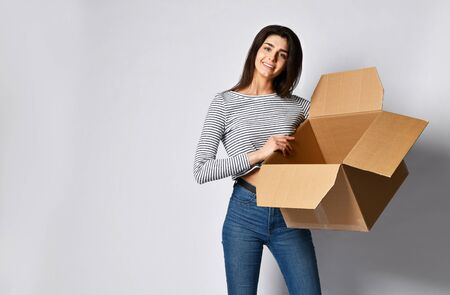 Surprised beautiful brunette woman standing on a light background with a moving cardboard box. shows that the box is empty Stock Photo