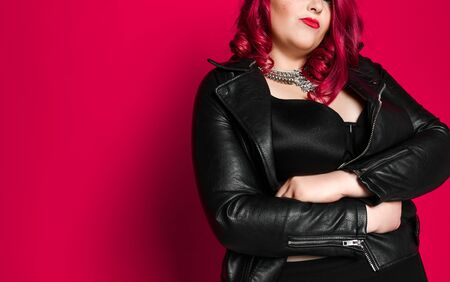 Portrait of beautiful plus size sexy red-haired woman in black leather jacket and black bra, on pink studio background. She folded her arms across her chest. closed pose, arrogance. Hot stuff
