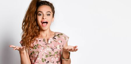 Young cute long-haired woman in a floral pink fashionable dress raised her hands in surprise on a white background