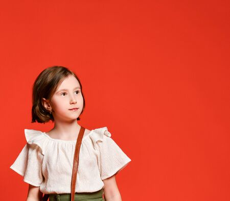 Little cute girl in khaki skirts and light blouse with a straw hat and a straw bag posing on a red terracotta background. 스톡 콘텐츠
