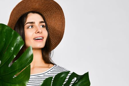 Portrait of a stylish serious girl wearing a straw hat, posing next to an exotic plant. Amazing brunette in casual clothes, standing on a light background with large green leaves. 스톡 콘텐츠
