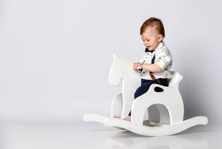 Funny baby sitting on the toy horse in white studio background