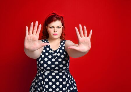 Serious young caucasian size woman plus showing stop gesture with her hand. She dressed in a polka dot dress in the studio on a red background Stock Photo