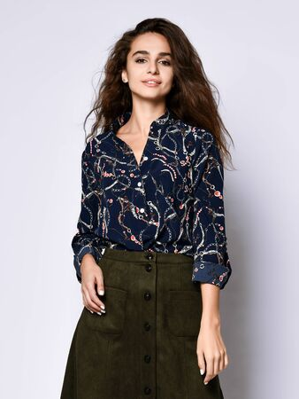 Vertical of a short beautiful cheerful young woman posing in solitude, in a dark silk blouse with floral patterns, a dark short skirt with buttons , looking with a smile Stock Photo