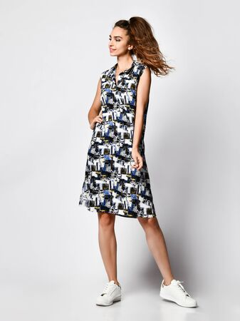 Young cute long-haired woman posing in a new floral black and white dress with a fashionable pattern in sneakers, happy full body smiles on a white background