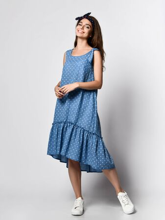 Slim curly female model in a silk pale denim long dress looking at the camera in full growth. . Cute girl in romantic clothes is going on a date, smiling pretty on a white background. Stok Fotoğraf
